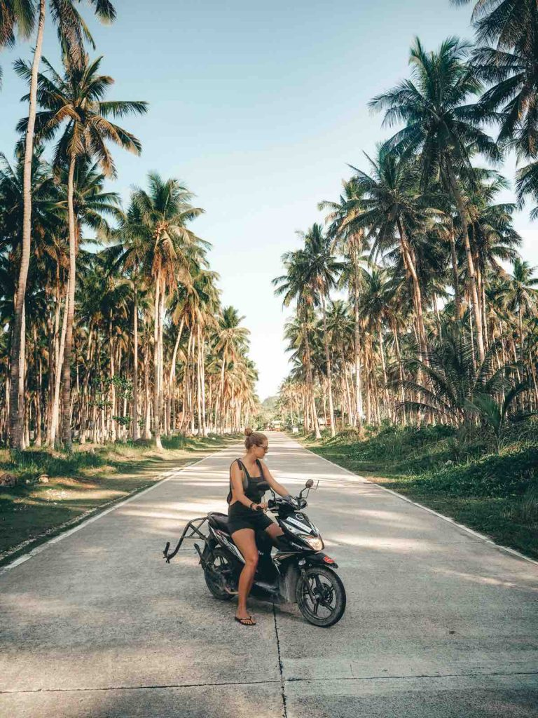 Riding a scooter along the palm tree roads of Siargao Island