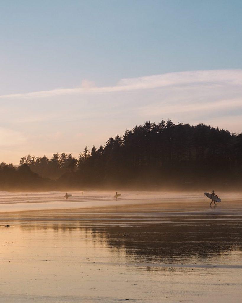 Surfers at Cox Bay at sunset